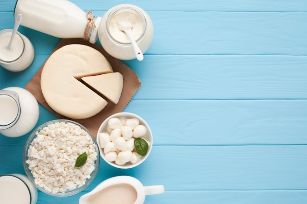 Jars of milk and cut cheese wheel Premium Photo