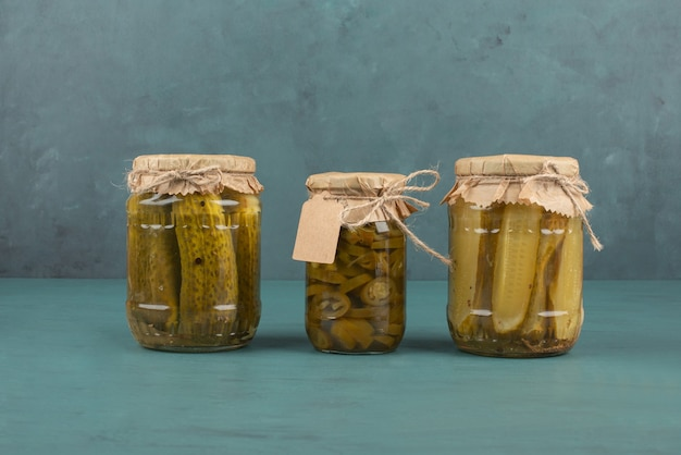 Jars of pickled cucumbers and jalapenos on blue table. Free Photo
