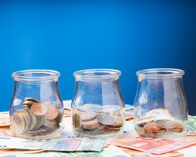 Jars with coins on banknotes Free Photo