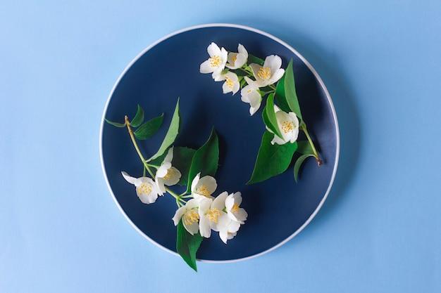 Цветы жасмина на синей тарелке Premium Фотографии