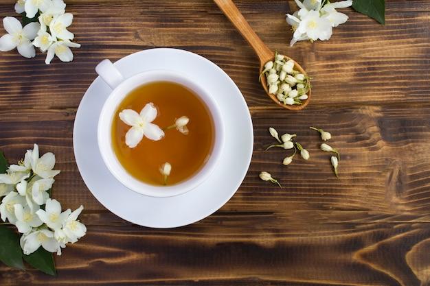 Жасминовый зеленый чай в белой чашке на коричневой деревянной поверхности, вид сверху, копия пространства Premium Фотографии