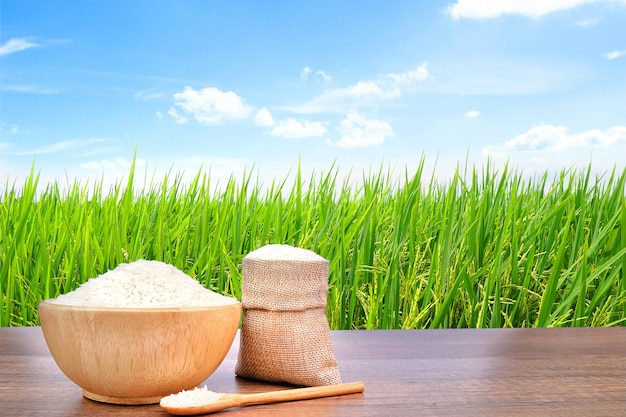 Jasmine rice in wooden bowl and sackcloth burlap on vintage wooden table with the green rice field. Premium Photo