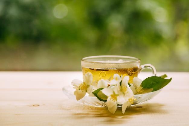 Жасминовый чай в мягком теплом вечернем свете со свежими цветами жасмина Premium Фотографии