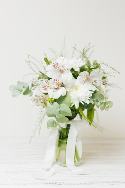 Jasminum auriculatum flower vase with white ribbon on wooden table Free Photo