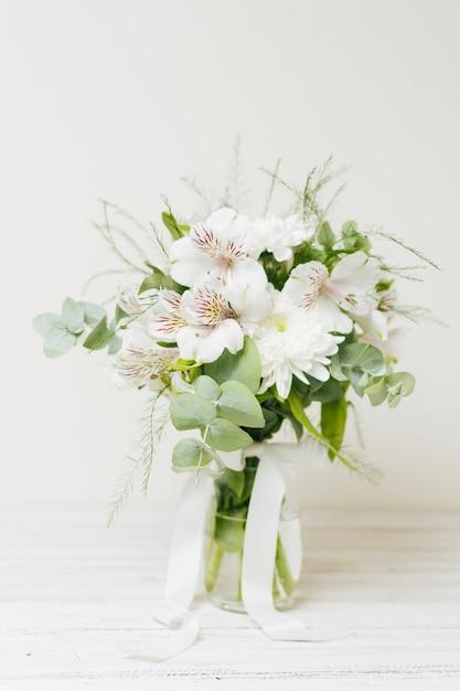 Ваза для цветов jasminum auriculatum с белой лентой на деревянном столе Бесплатные Фотографии