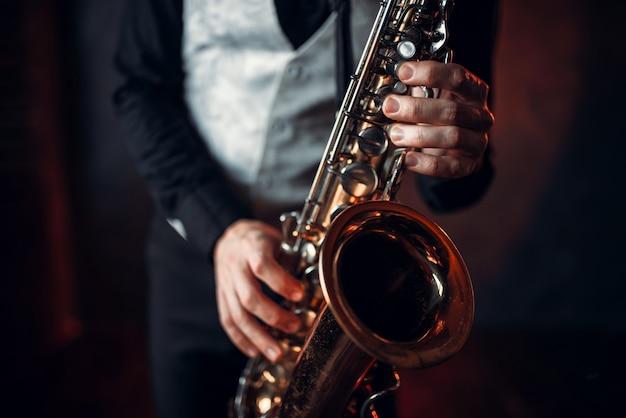 Джазовый человек вручает саксофон крупным планом. музыкальный инструмент духовой оркестр. Premium Фотографии