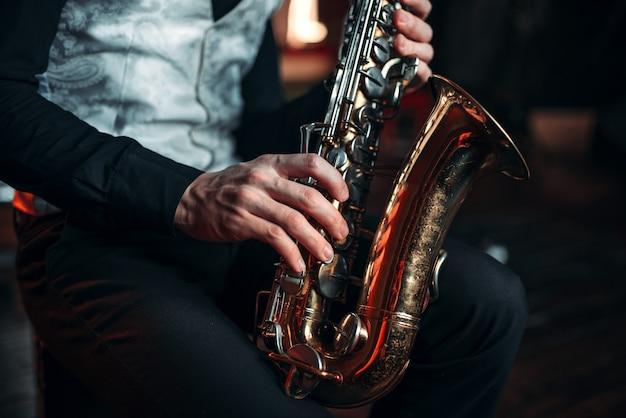 Джазовый человек руки, держа саксофон крупным планом Premium Фотографии