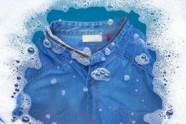 Jean shirt soak in powder detergent water dissolution. laundry concept Premium Photo