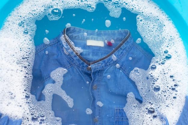 Jean shirt soak in powder detergent water dissolution, washing cloth. Premium Photo