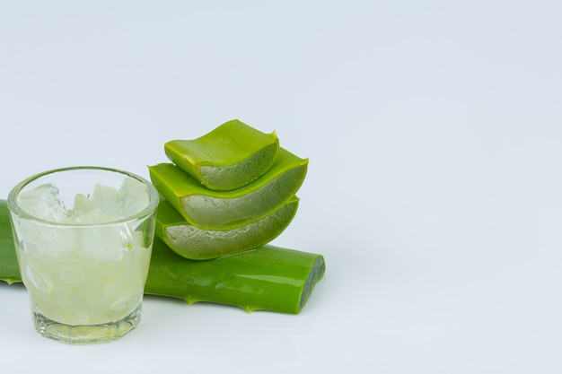 Jel of aloe vera in a glass with aloe vera leave is near together on white wall. Free Photo