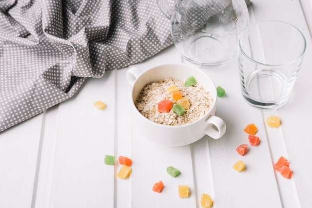 Jelly candies in the bowl of oat on the white table Free Photo