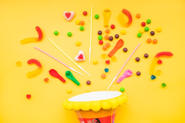 Jelly candies and candles over the party hat against yellow background Free Photo