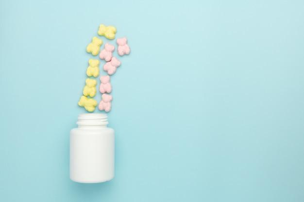 Желе плюшевого мишку витамин жевательные конфеты, посыпать из бутылки на синем фоне. рекламная концепция медицины для детей Premium Фотографии