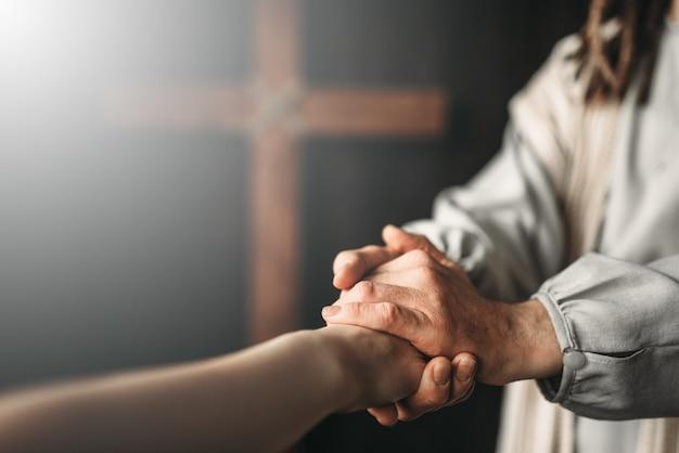 Иисус христос в белом одеянии протягивает руку помощи верным Premium Фотографии