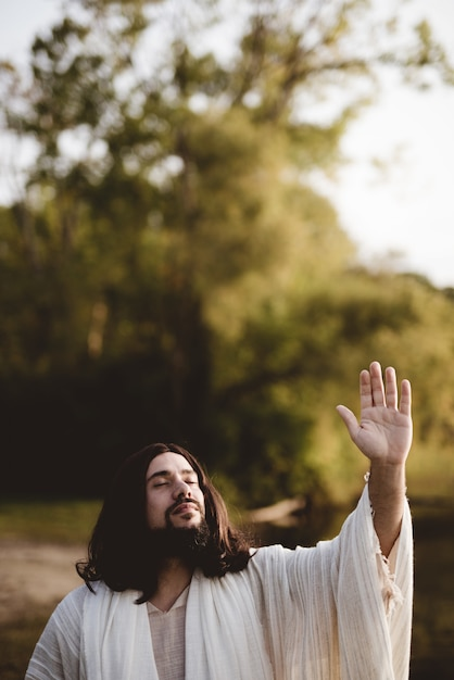 Jesus christ whit his hand up towards the sky while his eyes are closed Free Photo