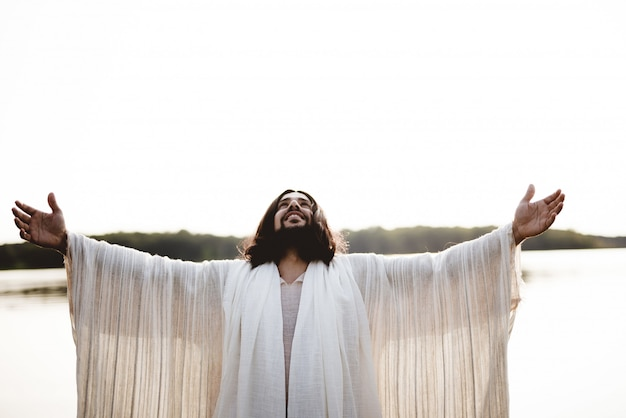 Jesus christ with his hands towards the sky Free Photo