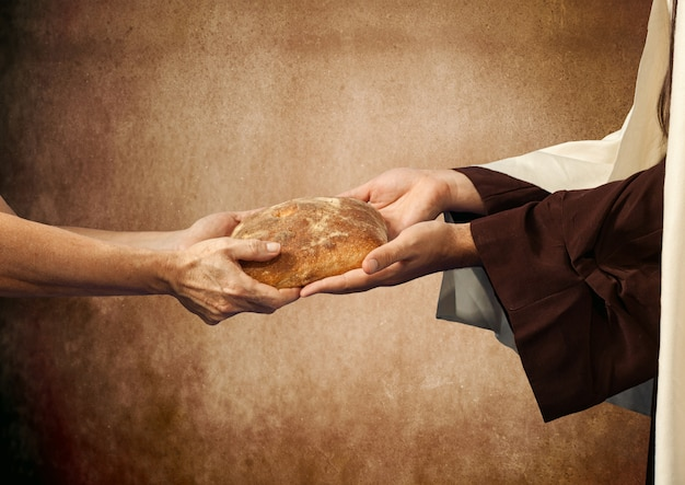 Jesus gives the bread to a beggar. Premium Photo