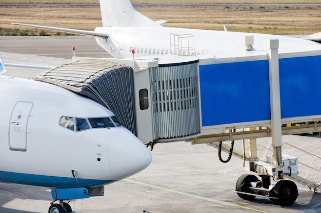 Jetway is served to passenger airplane at airport. Premium Photo