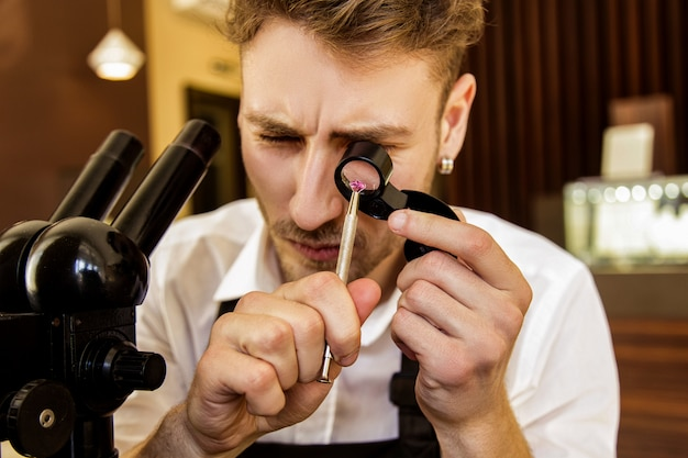 The jeweler examines the gem under the magnifying glass Premium Photo