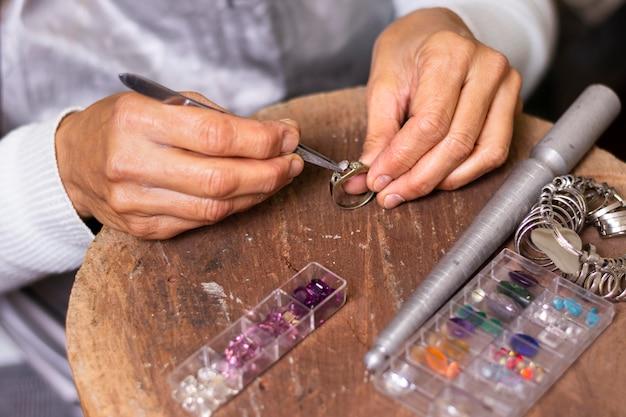 宝石商の手がリングの高いビューに宝石を置く 無料写真