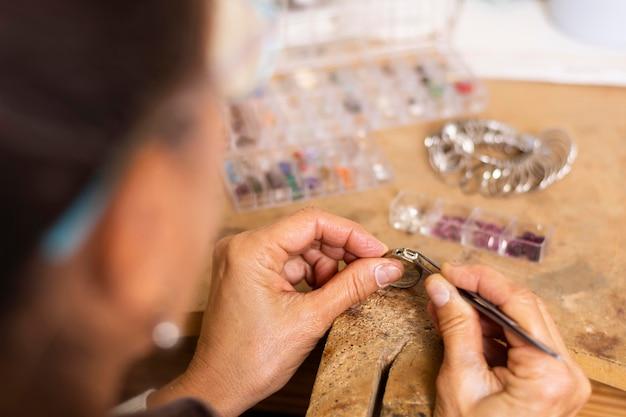 宝石商の手が宝石をリングに置く 無料写真