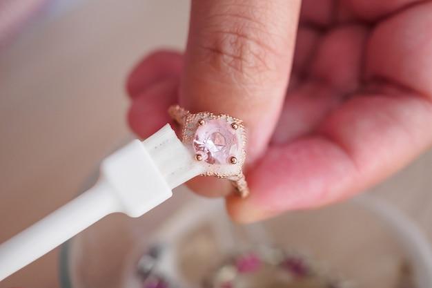 宝石商の手によるクリーニングと研磨ヴィンテージジュエリーダイヤモンドリングのクローズアップ Premium写真