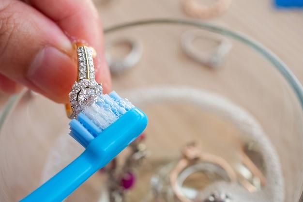 宝石商の手の洗浄とビンテージジュエリーダイヤモンドリングのクローズアップを研磨 Premium写真