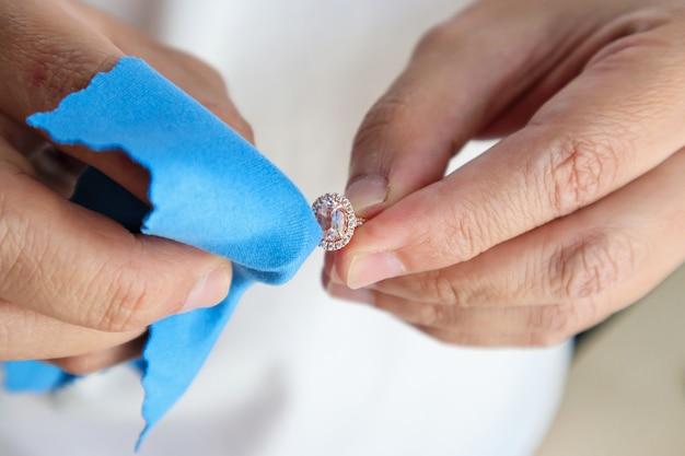 マイクロファイバーファブリックを使用したジュエリーダイヤモンドリングの手作業による研磨とクリーニング Premium写真