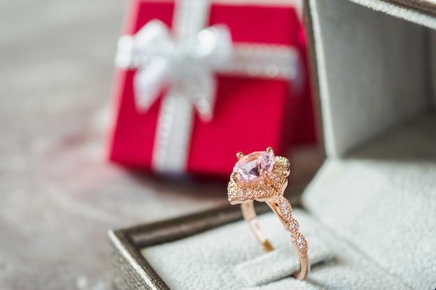 빨간 선물 상자 배경으로 보석 핑크 다이아몬드 반지 프리미엄 사진