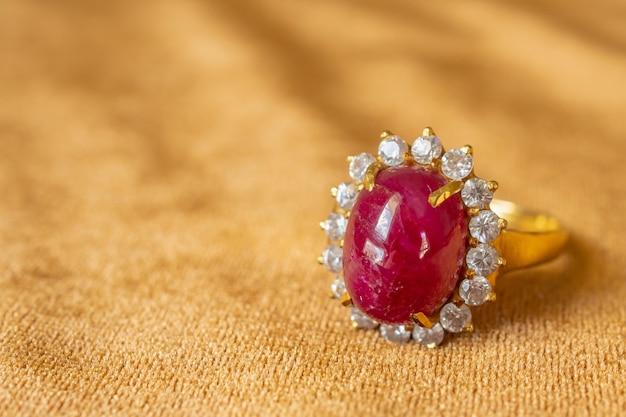 황금 직물 배경에 보석 붉은 루비 반지를 닫습니다. 프리미엄 사진
