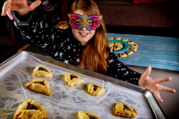 Еврейская девушка с длинными волосами развлекается и танцует в маске с печеньем. Premium Фотографии