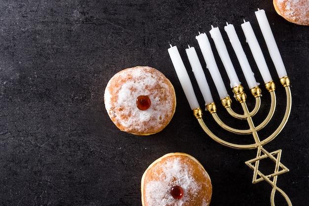 Jewish hanukkah menorah and sufganiyot donuts on black top view copy space Premium Photo