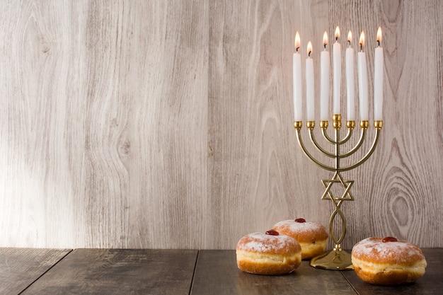 Jewish hanukkah menorah and sufganiyot donuts on wooden table copy space Premium Photo