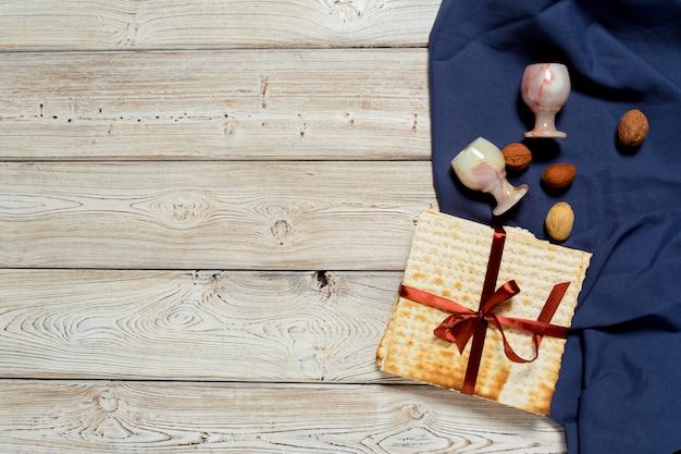 Jewish holiday passover banner design with wine, matzo on wooden background. Premium Photo