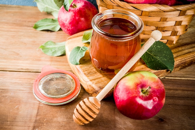 Jewish holiday rosh hashanah or apple feast day concept, with red apples, apple leaves and honey in jar Premium Photo