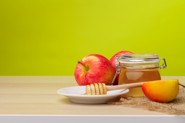 Jewish holiday rosh hashanah with honey and apples on wooden table. Premium Photo