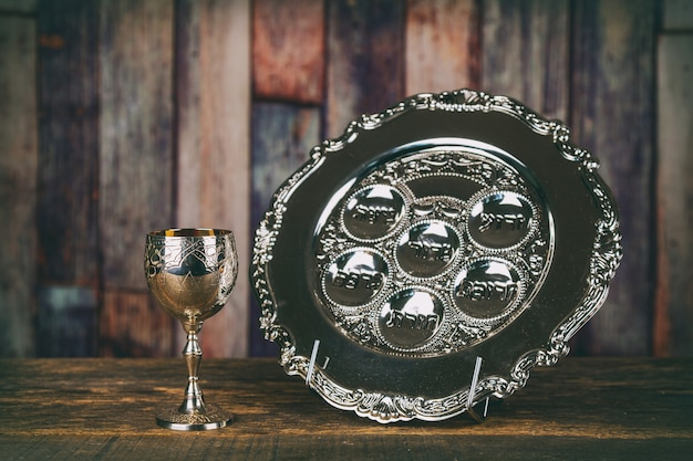 Jewish holidays passover pesach matzah and a silver cup full of wine with a traditional blessing Premium Photo