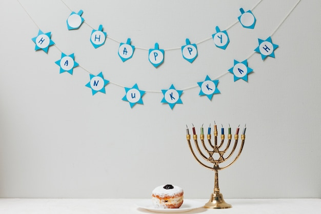 Jewish menorah and a donut on a table Free Photo