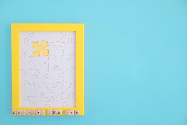 Наружная коробка головоломка желтая рамка с белыми кусками челюсти jig на синем фоне Бесплатные Фотографии