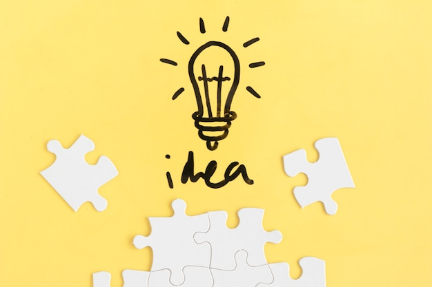 Jigsaw puzzle and light bulb with idea word on yellow background Free Photo