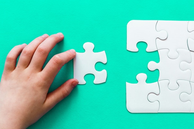 Jigsaw puzzle with missing piece on mint background people hand Premium Photo