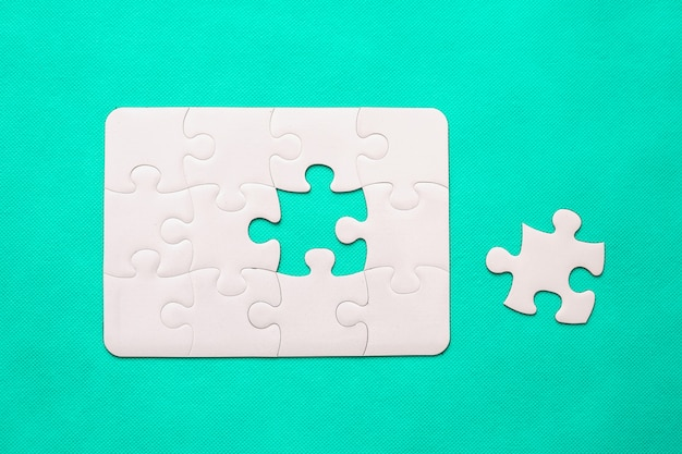 Jigsaw puzzle with missing piece on mint background top view Premium Photo