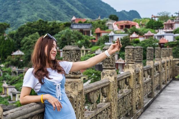 Женщина с помощью смартфона для селфи фото в jiufen, тайвань Premium Фотографии