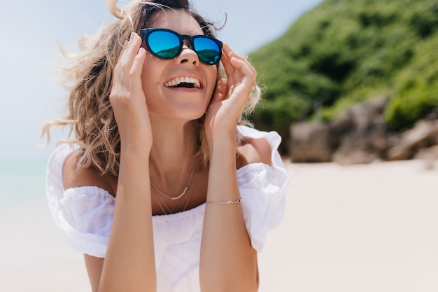 Jocund tanned lady in summer clothes looking at sky with cheerful smile. outdoor photo of good-humoured woman in elegant sunglasses enjoying rest at resort. Free Photo