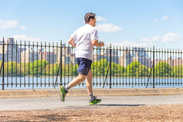 Jogger running along central park reservoir in new york. central park is full of active people throughout the year. Premium Photo
