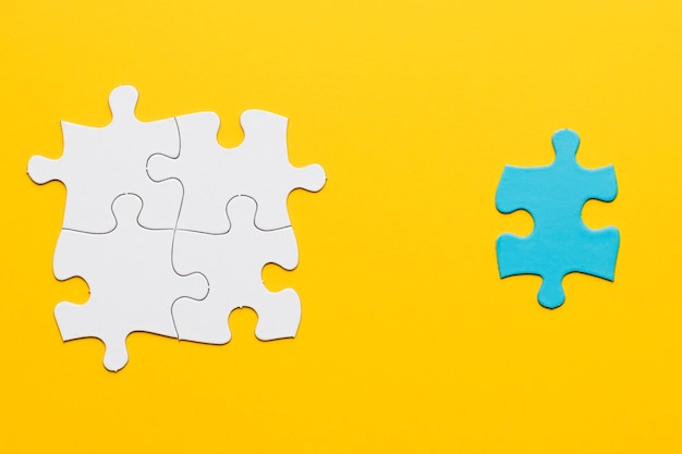 Joint white puzzle with a blue single piece on yellow surface Free Photo