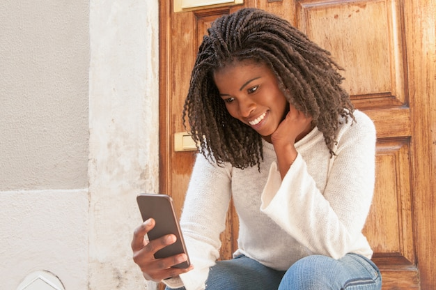 Jolly black woman reading lovely sms from boyfriend Free Photo