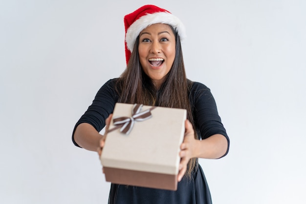 Jolly christmas lady giving gift Free Photo
