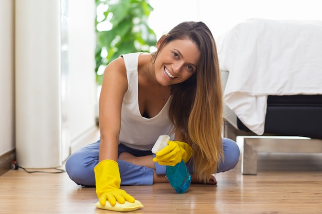 Jolly young maid cleaning floor with cloth Free Photo