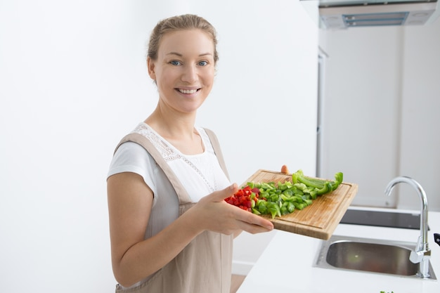 Jolly young woman showing cut fresh bell pepper Free Photo
